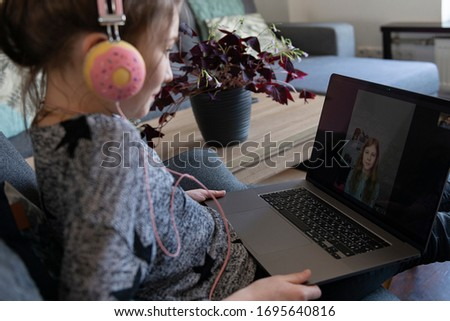 Stay at home quarantine coronavirus pandemic prevention. Teen girl communicates with a laptop with her close friend, learning, communication, entertainment.