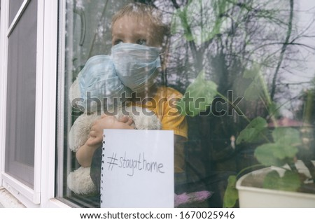 Stay at home quarantine for coronavirus pandemic prevention. Child and his teddy bear both in protective medical masks sits on windowsill and looks out window. View from street. Prevention epidemic.