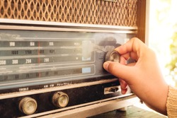 Stay at home retro lifestyle - Woman hand adjusting the button vintage radio receiver for listen music or news - vintage color tone effect.