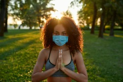 Stay calm. Young mixed race woman wearing protective face mask keeping palms together and looking at camera while practicing yoga outdoors in nature during covid19 pandemic. Healthy lifestyle concept
