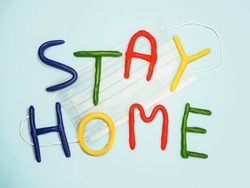 Stay home plasticine colorful letters. Light blue background with surgical facial mask. Stay home text in multi colored letters. Coronavirus, lockdown, safety concept. Kids, child worry about virus