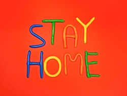 Stay home plasticine colorful letters. Red background. Stay home text in multi colored letters. Pandemic, coronavirus, lockdown, safety concept. Kids, child worry about the virus