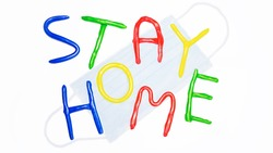 Stay home plasticine colorful letters. White background with surgical medical mask. Stay home text in multi colored letters. Coronavirus, lockdown, safety concept. Kids, child worry about virus