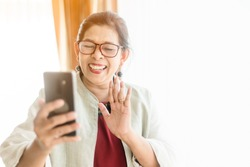Stay home save lives from coronavirus covid-19.Self isolation.Happy smiley face senior elderly woman using smartphone video call conference camera and talking with family.Video chat social distancing.