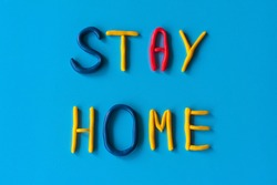 Stay home words from letters made of clay on a blue background, flat lay, background with text.