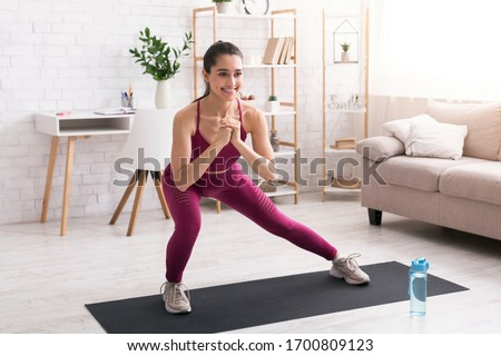 Stay home workout. Happy millennial girl doing lunges on yoga mat in light room Foto stock ©