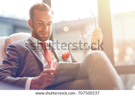 Stay informed. Cheerful professional handsome businessman reading a newspaper and resting while sitting in the departure lounge
