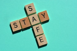 Stay Safe, words in 3d wood alphabet letters in crossword form isolated on blue background