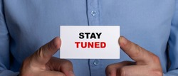 Stay tuned written on a white card in the hands of a man in black and red letters