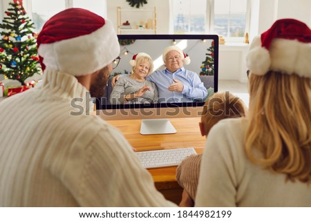 Staying at home but keeping in touch with family. Mom, dad and little son video calling grandparents on Christmas holidays. Happy grandma and grandpa talking to their grandchild who they miss so much