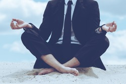 Staying calm. Close-up of businessman meditating while sitting in lotus position on sand and against blue sky