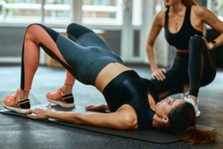 Staying fit. Young caucasian woman in sportswear lying on yoga mat at gym and doing abs exercises with assistance of personal trainer or fitness instructor