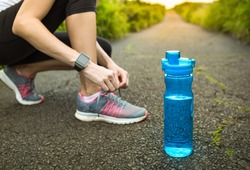 Staying hydrated and drinking water concept. Woman getting ready for run with bottle of water next to her. Focus on bottle of water.