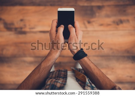Staying in touch. Top view of man holding smart phone while standing on the wooden floor