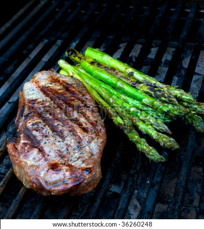 Steak and asparagus on hot barbecue grill