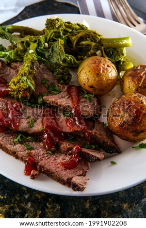 Steak and new potatoes with honey mesquite barbecue sauce and garlicky broccoli rabe Foto stock ©