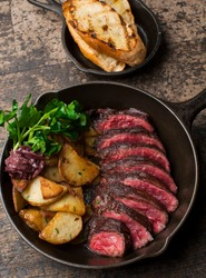 Steak and potatoes. Grade A grass fed angus beef steaks. Tenderloin, filet mignon, New York strip, bone in rib-eye grilled medium rare on outdoor wood-fired grill. Classic American steakhouse entree.