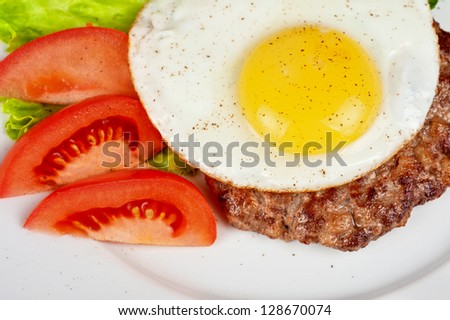 steak beef meat with fried egg, tomato, cucumbers and salad