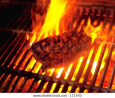 Steak cooking on flame grill