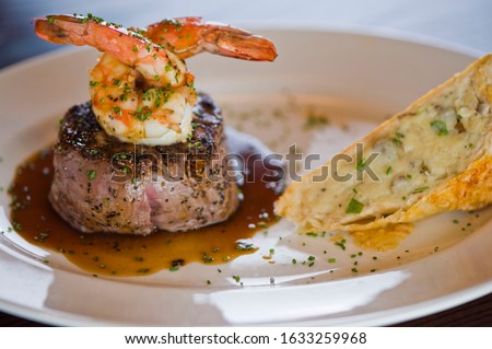 Steak filet and Jumbo Shrimp. Grade A, grass fed angus beef. Traditional classic New York steakhouse menu favorite. Filet topped with jumbo shrimp and served with garlic bread.