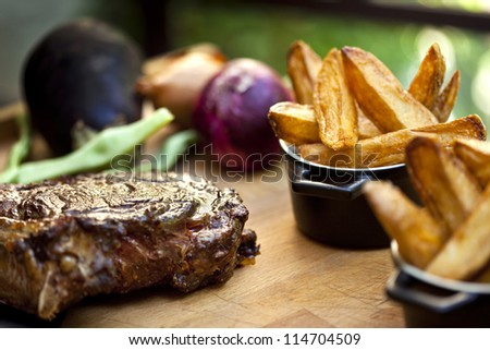 Steak, fried potatoes, and vegetables on a wooden board