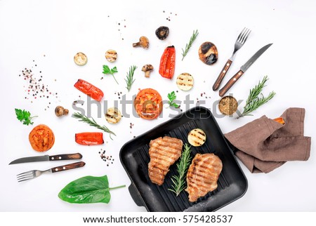 Steak grill in the cast iron grill pan on a white background with a variety of grilled vegetables Top view. Flat lay #575428537