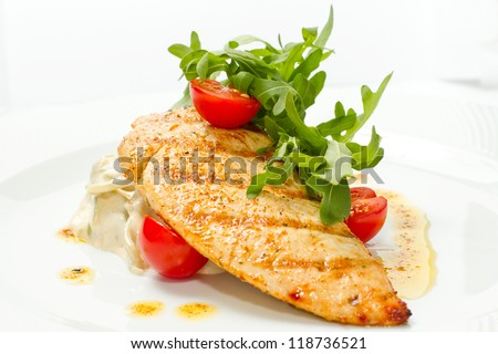 steak is the fried hen with a tomato on a white dish