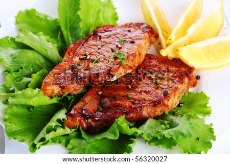 Steak meat grilled with lemon and lettuce - stock photo