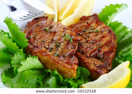 Steak meat grilled with lemon and lettuce