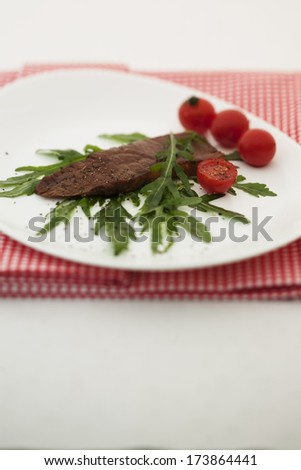 Steak on arugula and tomato salad.