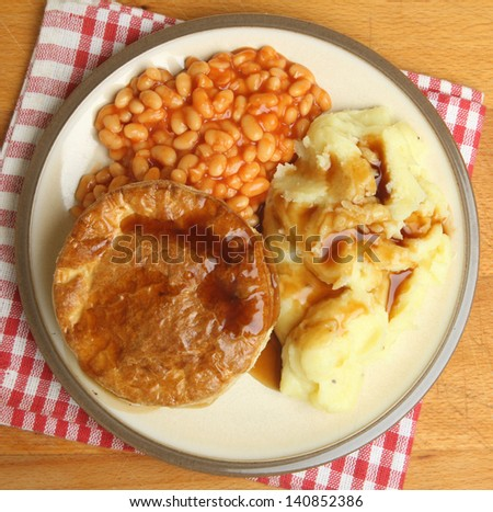 Steak pie with baked beans, mashed potato and gravy.