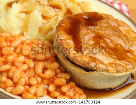 Steak pie with mashed potato and baked beans.
