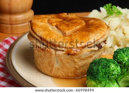 Steak pie with mashed potato, broccoli and gravy.