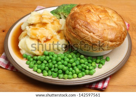 Steak pie with mashed potato, vegetables and gravy.