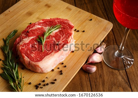 Steak Raw meat. Black Angus Prime meat steaks. Rib Eye Steak, dry Aged Wagyu Entrecote  Ribeye Steak with seasoning on dark wooden background. Top view. Rosemary leaves, Garlic, salt, pepper, red wine