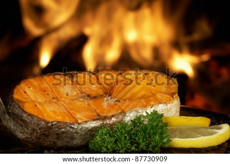 Steak salmon grilled on fire background