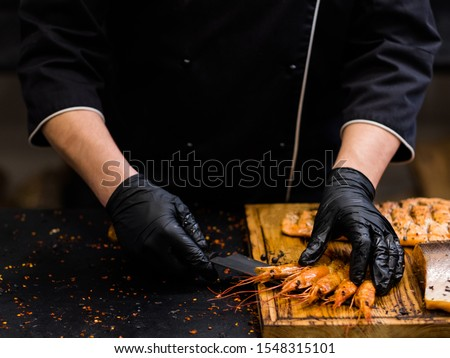 Steakhouse and seafood restaurant. Chef in black cooking gloves serving smoked langoustines on wooden board.