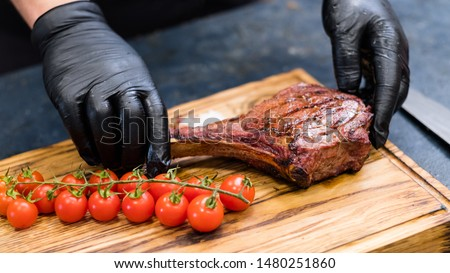 Steakhouse kitchen. Chef hands serving Cowboy steak with cherry tomatoes on wooden board.