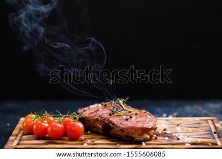 Steakhouse menu. Rib eye steak. Closeup of grilled beef meat with cherry tomatoes and burning rosemary twig. Copy space.