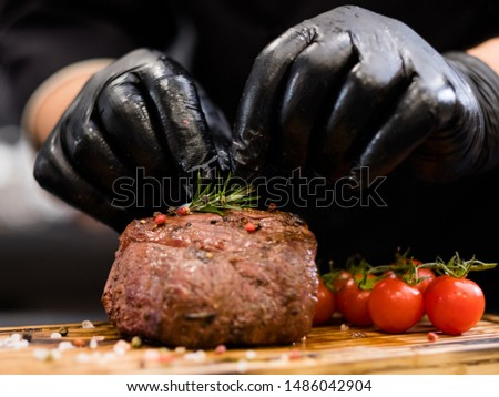Steakhouse menu. Tenderloin steak. Chef hands serving grilled beef meat with cherry tomatoes and rosemary twig.