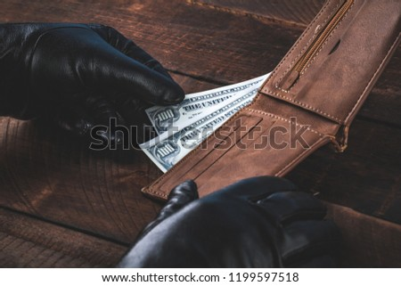 Stealing money from a wallet. Theft concept. Сток-фото ©