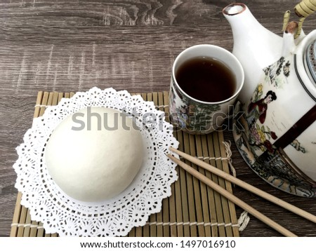 steam bao on paper lace with chopsticks and chinese tea #1497016910