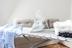 Steam blue iron on ironing board.  Hot electric iron. Clothes, ironing board household concept.