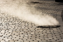 Steam coming out of manhole in a street of Paris