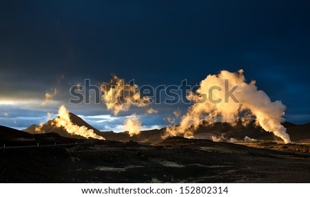 Steam erupting from geothermal power station at sunset, yellow light of setting sun back-lighting the columns of steam, Myvatn area, Iceland