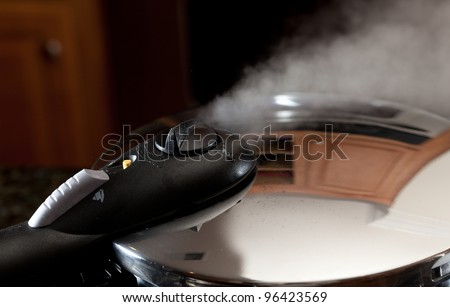 Steam escaping from lid of pressure cooker with reflection of modern kitchen
