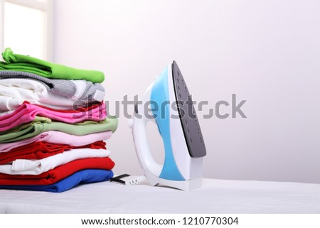 Steam iron and a pile of ironed clothes on an ironing board