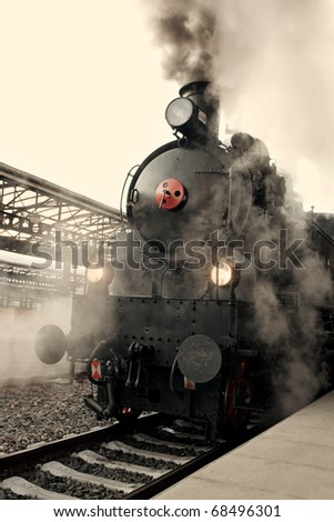 Steam locomotive at the railway station wrapped up in cloud - vintage retro tinting