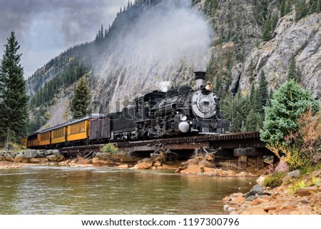 Steam Locomotive on a trestle bride, crossing a river in the mountains.