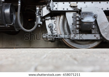 Steam locomotive wheels or steam train wheels and rods closeup for background #658071211